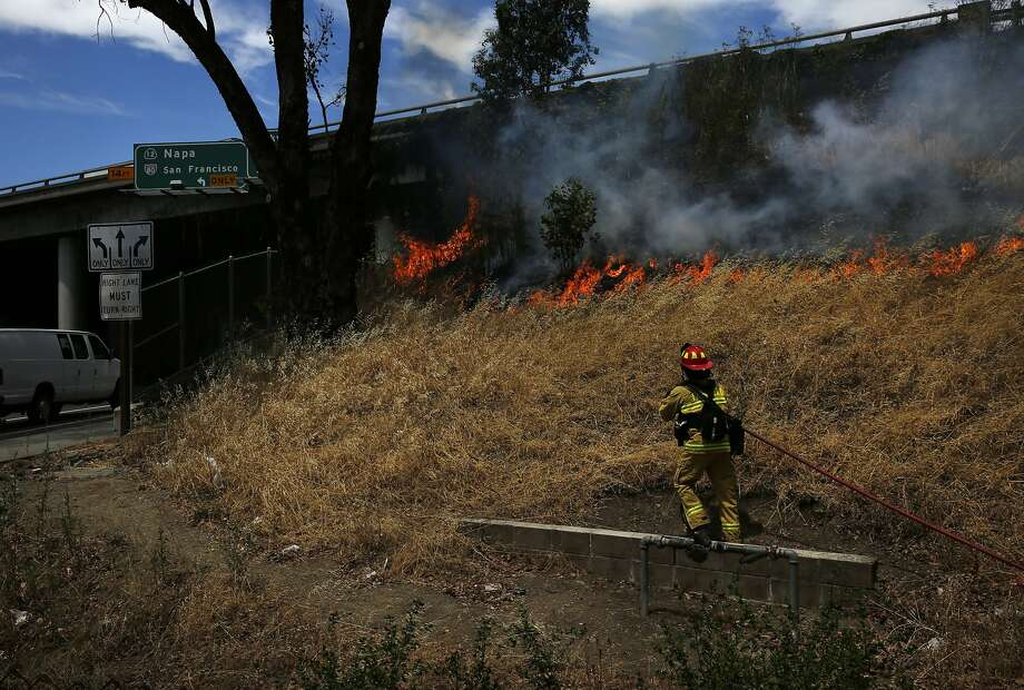 A firefighter moves in to put out a brush fire that broke out along the side of I80 July 6, 2015 in Fairfield, Calif. Photo: Leah Millis, The Chronicle