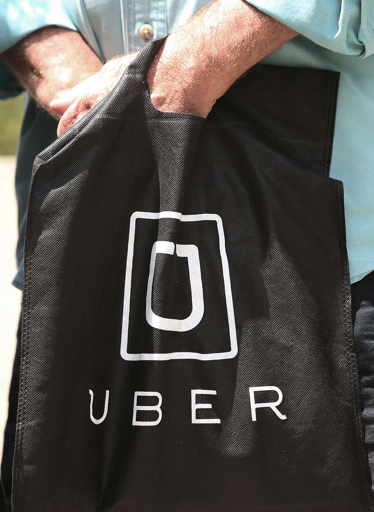 An Uber driver holds an Uber bag during a press conference at the plaza entrance of 450 Golden Gate Ave. in San Francisco, Calif., on Thursday, August 6, 2015. Boutrous and Uber drivers discuss the O'Conner vs. Uber lawsuit seeking to reclassify Uber drivers in California as employees.