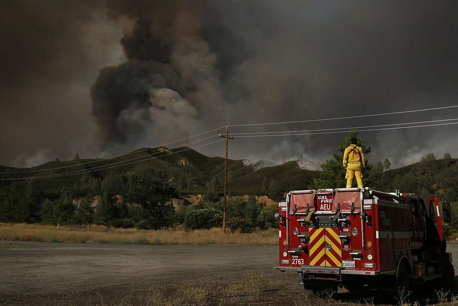 Fernando Solis from Cal Fire Amador watches as the Rocky Fire burns off of highway 20 while taking a break after a long shift August 3, 2015 in Lake County, Calif. Photo: Leah Millis, The Chronicle