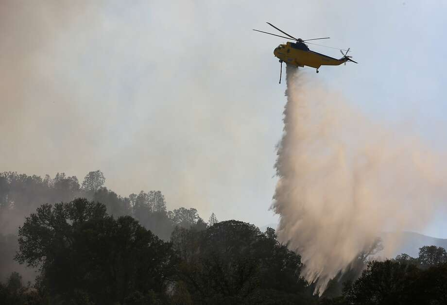 A helicopter drops water on the Rocky Fire near Highway 20 in Lake County on Monday. Photo: Leah Millis, The Chronicle