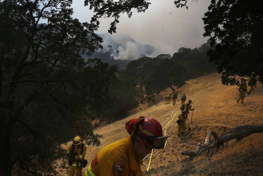 Crews hike into a burning canyon July 23 to fight the Wragg Fire east of Lake Berryessa near Highway 128 and Pleasants Valley Road. The blaze has consumed almost 70,000 acres. Photo: Leah Millis, The Chronicle