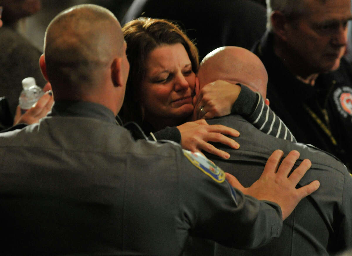 People rise, applaud and console the first responders as they enter the room during an interfaith vigil for the families and residents affected by the Sandy Hook Elementary School shooting at Newtown High School in Newtown, Conn., on Sunday, Dec. 16, 2012.