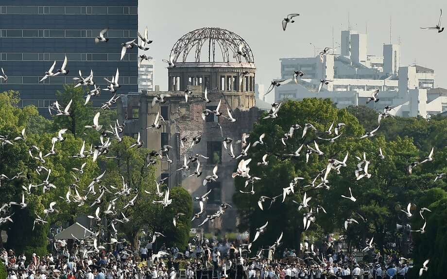 Doves fly over the Hiroshima Peace Memorial Park in western Japan on August 6, 2015 during a memorial ceremony to mark the 70th anniversary of the atomic bombing of Hiroshima.  Tens of thousands gathered for peace ceremonies in Hiroshima August 6 on the 70th anniversary of the atomic bombing that helped end World War II, but still divides opinion today over whether the total destruction it caused was justified.  Photo: Kazuhiro Nogi, AFP / Getty Images