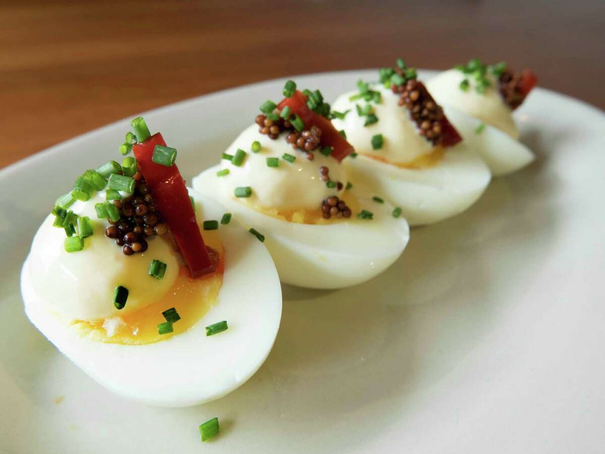 Not your mama's deviled eggs: Slowly simmered eggs yield a still-soft yolk topped with Kewpie mayonnaise pickled mustard seeds and a slice of Calabrese pepper.