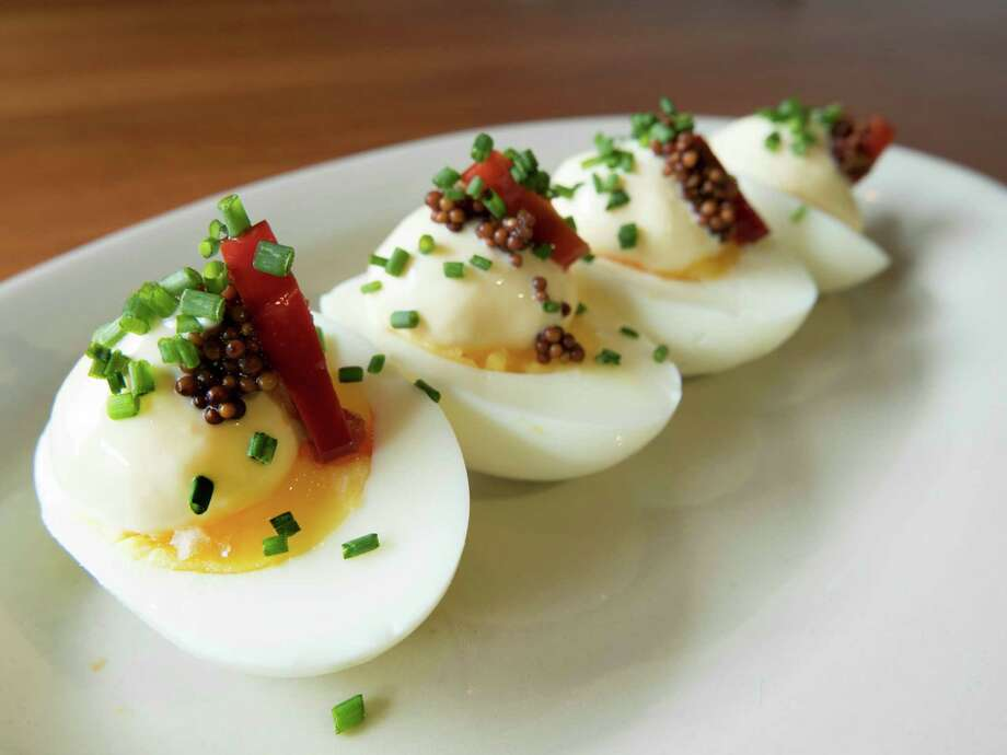 Not your mama's deviled eggs: Slowly simmered eggs yield a still-soft yolk topped with Kewpie mayonnaise pickled mustard seeds and a slice of Calabrese pepper. Photo: Billy Calzada /San Antonio Express-News / San Antonio Express-News