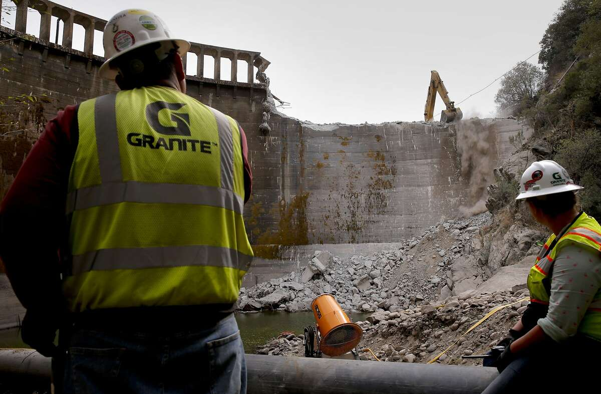 Granite Construction workers Cedric Chuigo, (left) and Alison Elwell watch from below the demolition of the San Clemente Dam in Carmel Valley, California, as seen on Tues. August 4, 2015.