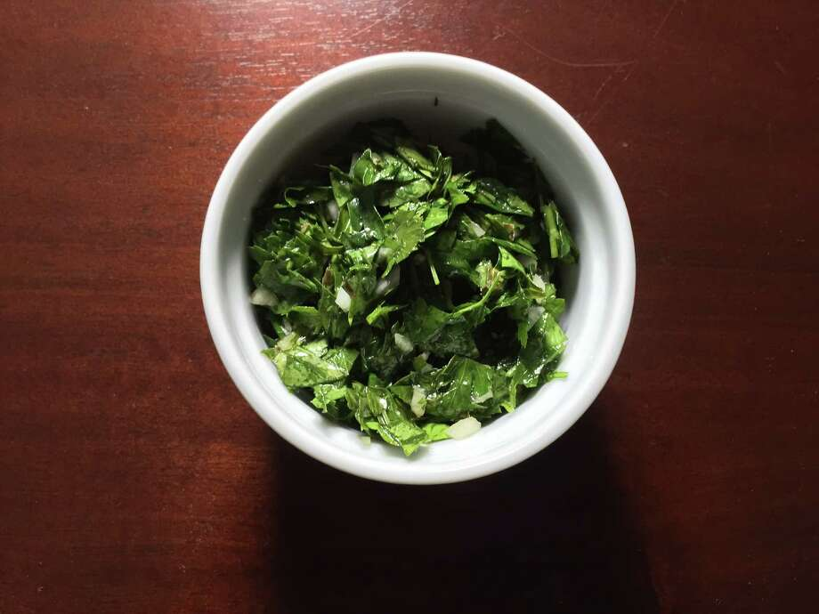 Chimichurri, a mixture of minced parsley, onion, olive oil, vinegar and oregano, is a classic Argentinian condiment for grilled meats. Photo: Edmund Tijerina /San Antonio Express-News