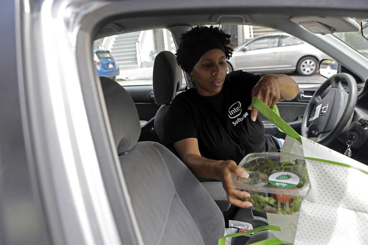 """TaNica Lyons of San Francisco makes a lunch delivery for Sprig, a meal delivery service, in San Francisco, Ca. on Thursday, Aug. 6, 2015. """"I have lived here all my life and sometimes I'm like 'oh wow, I have never been here before',"""" Lyons says of being a delivery driver for Sprig. """"It helps me get to know the streets more."""""""