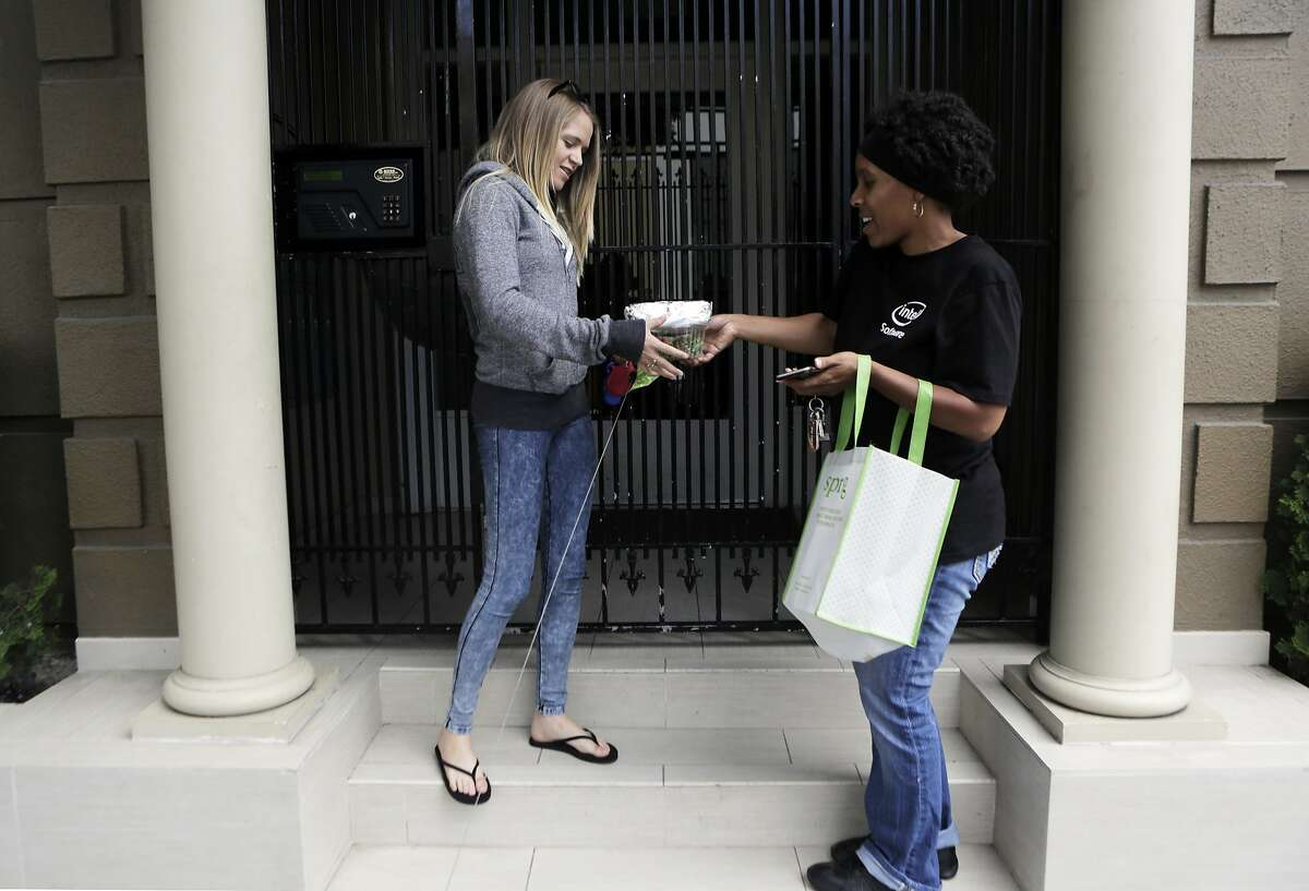 TaNica Lyons of San Francisco makes a lunch delivery to Collete Davis of San Francisco for Sprig, a meal delivery service, in San Francisco, Ca. on Thursday, Aug. 6, 2015.