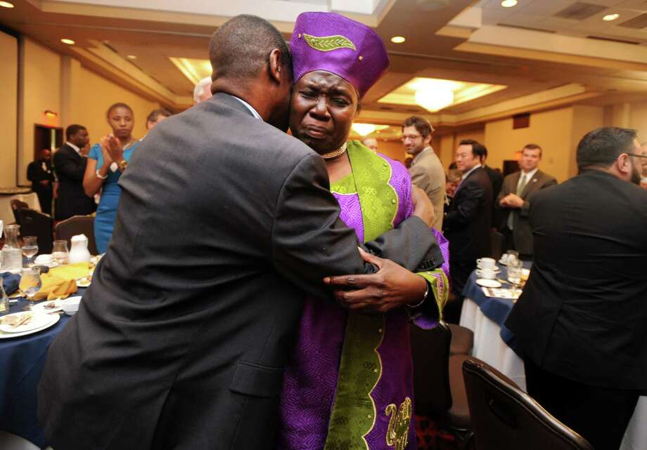The Rev. Mary McBride Lee hugs the Rev. Carl McCluster, of Shiloh Baptist Church on Thursday during a ceremony at the Bridgeport Holiday Inn to mark the signing of the 1965 Voting Rights Act. McBride Lee was honored at the event for her participation in the historic march in Selma, Ala., in 1965. Photo: Autumn Driscoll / Hearst Connecticut Media / Connecticut Post