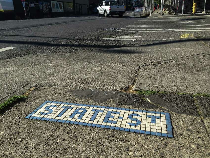 Looking north along 20th Avenue Northwest in Ballard, this marker is set in the sidewalk at the cross of Northwest 56th Street, showing the name of 56th before Ballard was annexed in 1907. While most, if not all the tiles along 24th were redone in the 1990s or later, most of those along 20th appear original, likely dating back to 1905.