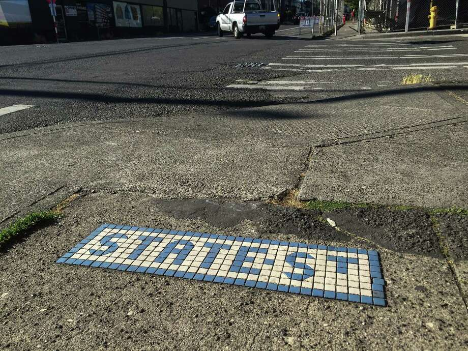 Looking north along 20th Avenue Northwest in Ballard, this marker is set in the sidewalk at the cross of Northwest 56th Street, showing the name of 56th before Ballard was annexed in 1907. While most, if not all the tiles along 24th were redone in the 1990s or later, most of those along 20th appear original, likely dating back to 1905. Photo: SEATTLEPI.COM