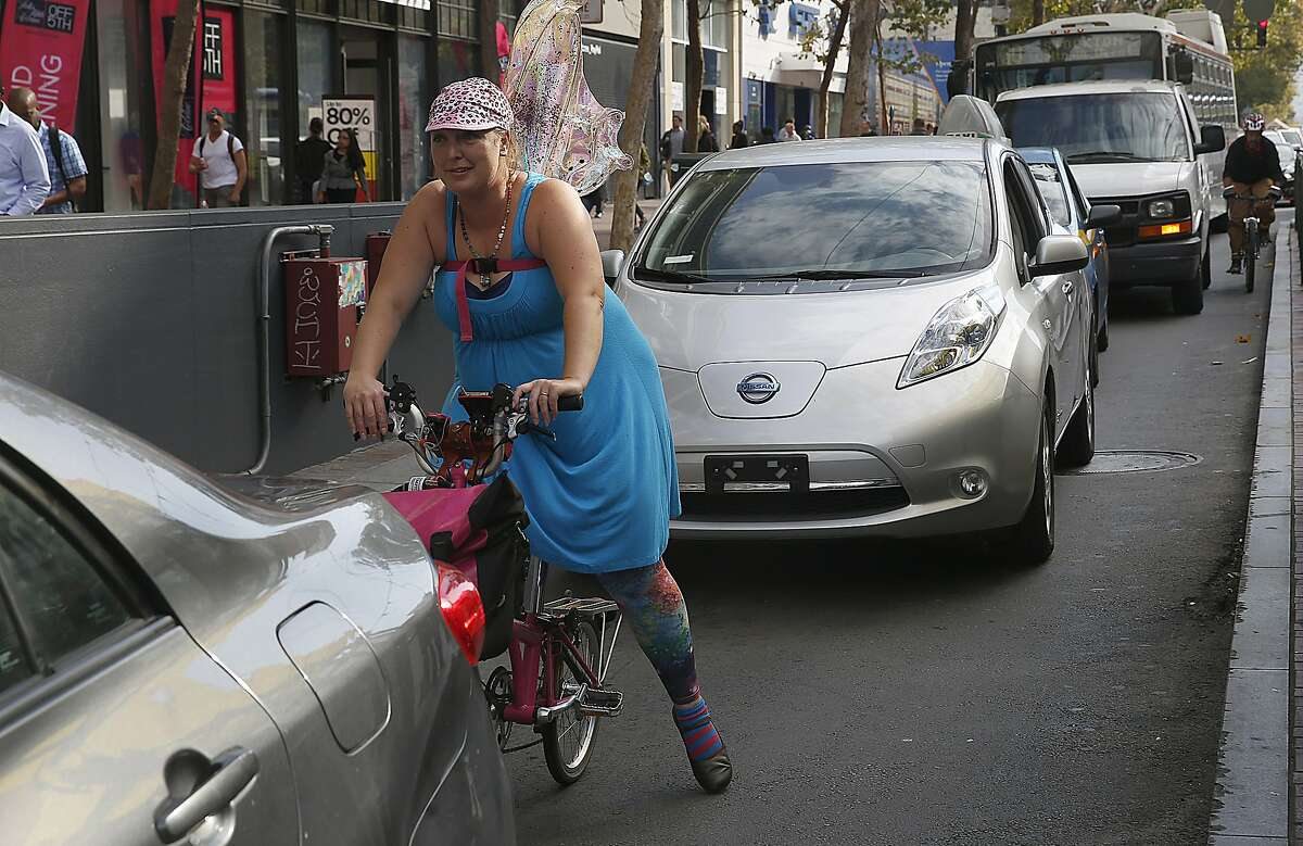 Lacy Love from Oakland uses her bike during rush hour traffic on Market at Mason streets in San Francisco, Calif., on Thursday, August 6, 2015.