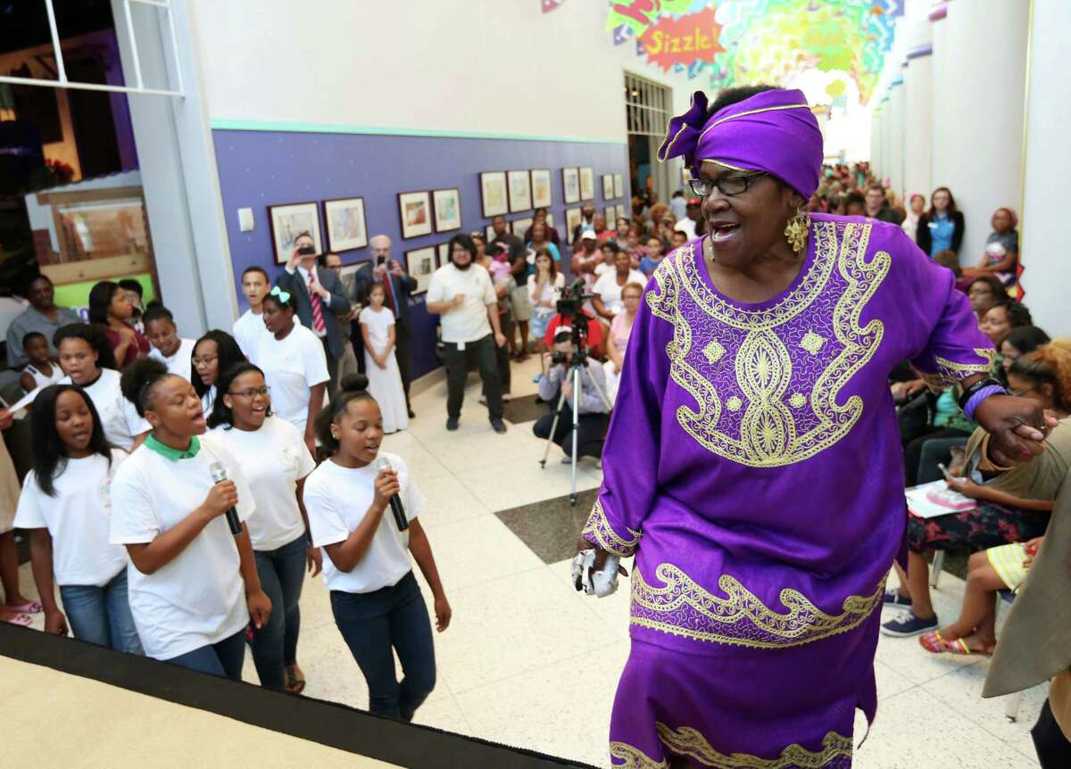 """Civil rights activist, Mamie King-Chalmers takes the stage while singing """"We Shall Overcome,"""" followed by members of the Community of Faith Youth Choir, at the Children's Museum of Houston Thursday, Aug. 6, 2015, in Houston. The Honey Brown Hope Foundation in partnership with Children's Museum of Houston presented """"History Talks"""" featuring Mamie King-Chalmers and her life's work."""