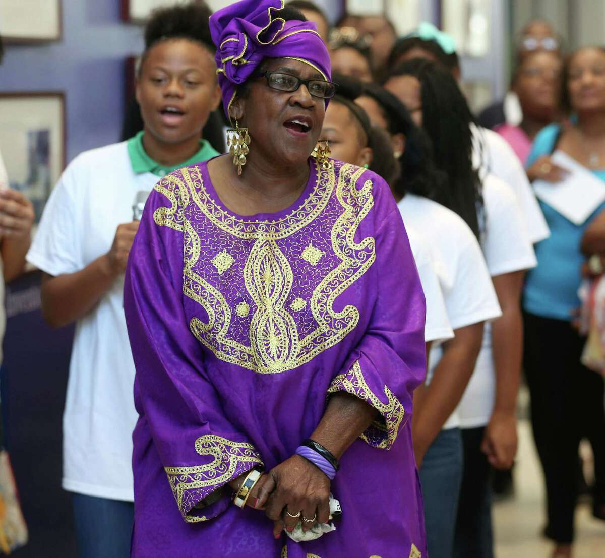 """Mamie King-Chalmers, center, sings """"We Shall Overcome"""" with members of the Community of Faith Youth Choir at an event celebrating her work as a civil rights activist, at the Children's Museum of Houston, Thursday, Aug. 6, 2015, in Houston. The event corresponded with the 50th anniversary of the Voting Rights Act of 1965."""