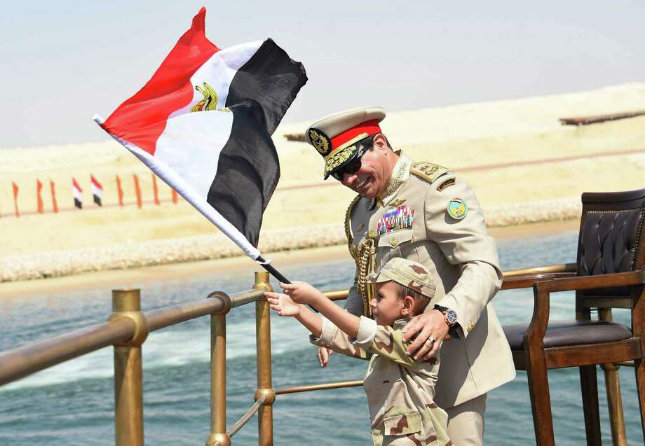 In this picture provided by the office of the Egyptian Presidency, Egyptian President Abdel-Fattah el-Sissi smiles at a boy dressed in a tiny military uniform as he waves the national flag from a monarchy-era yacht that sailed to the venue of a ceremony unveiling a major extension of the Suez Canal in Ismailia, Egypt, Thursday, Aug. 6, 2015. El-Sissi has billed the extension as an historic achievement needed to boost the country's ailing economy after years of unrest. (Egyptian Presidency via AP) MANDATORY CREDIT ORG XMIT: CAIMA801 Photo: Uncredited / Egyptian Presidency