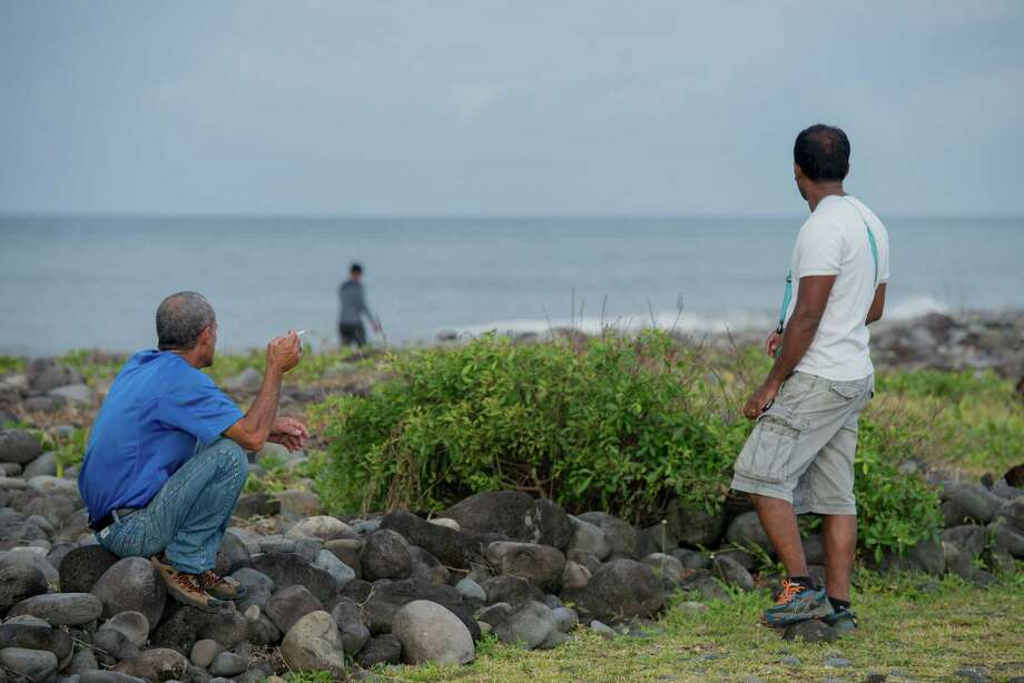 People walk on the beach of Saint-Andre, Reunion Island, in the hope of finding more plane debris, Thursday, Aug  6, 2015. Malaysian Prime Minister Najib Razak announced on Aug. 6 the washed-up debris was part of the wreckage of the missing Malaysian Airlines flight MH370. (AP Photo/Fabrice Wislez) ORG XMIT: XPAR101 Photo: Fabrice Wislez / AP