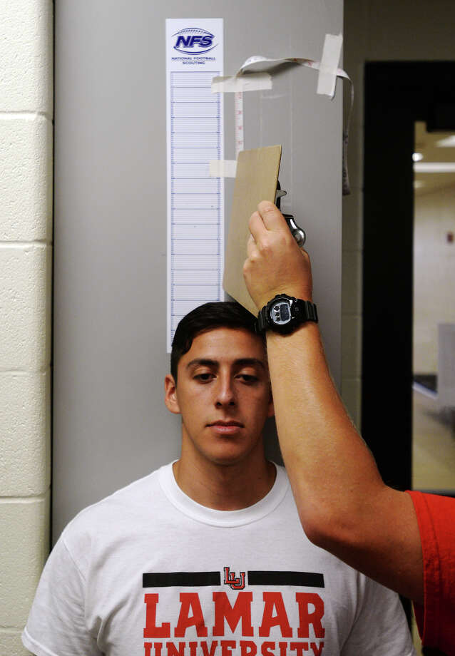 The Cardinals' Juan Carranco's height is recorded by athletic trainer Jeff Birchell on Thursday afternoon. Lamar Cardinal players took pre-season physical tests, including height, weight, and blood pressure, at the Dauphin Athletic Complex on Thursday afternoon. Photo taken Thursday 8/6/15 Jake Daniels/The Enterprise Photo: Jake Daniels / ©2015 The Beaumont Enterprise/Jake Daniels