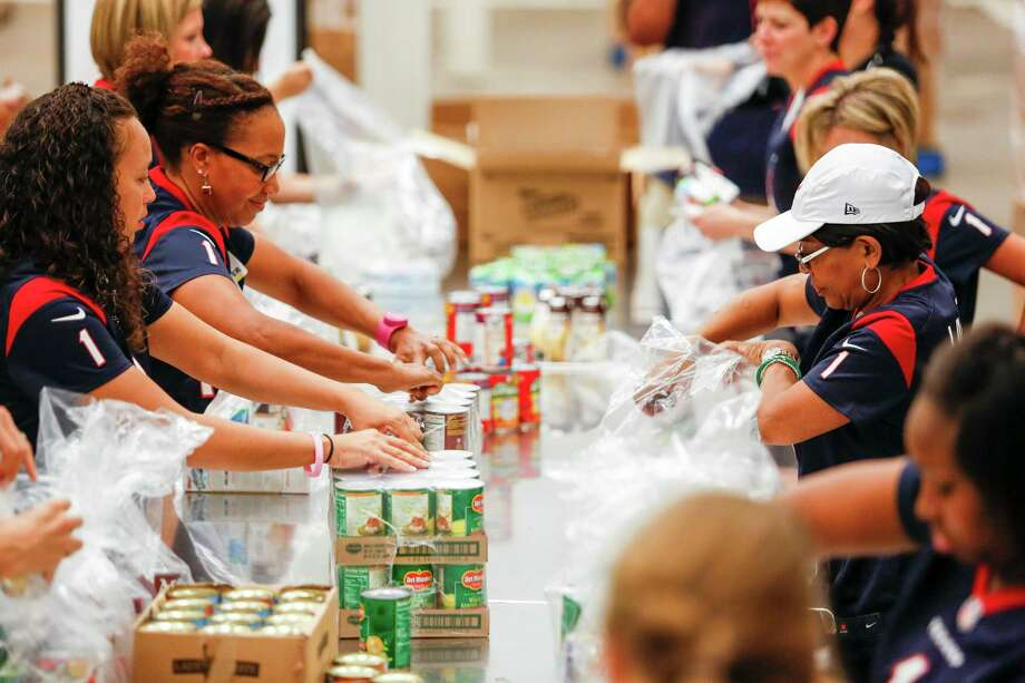 The Lady Texans fill backpacks as part of the Houston Food Bank's Backpack Buddy program Tuesday, Oct. 21, 2014 in Houston at the Houston Food Bank.  Many children who rely on free or reduced-priced lunches during the school year go home to meager or no meals on weekends. Houston Food Bank's Backpack Buddy program works to fill that gap by distributing packs with child-friendly, non-perishable, easily consumed and nutrient-dense food on Fridays at participating schools and other locations.Saturday Oct. 19, 2014 in Houston.  (Eric Kayne/For the Chronicle) Photo: Eric Kayne / Eric Kayne