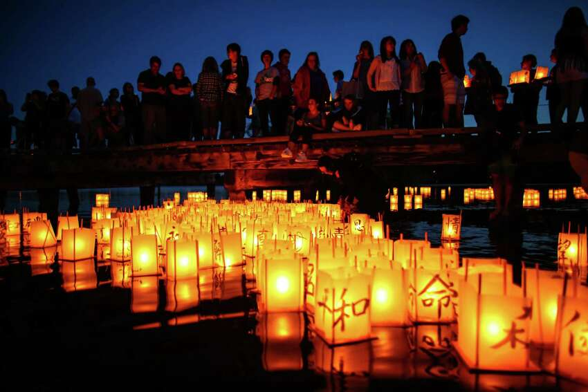 People gather Thursday at Green Lake to honor victims of the atomic bombings of Hiroshima, Nagasaki and other wars. Thousands of people gathered on a dock and the shore of Green Lake on the 70th anniversary of the U.S. use of the atomic bomb to launch floating lanterns. The date has been marked with a ceremony at Green Lake since 1984. Photographed on Aug. 6, 2015.