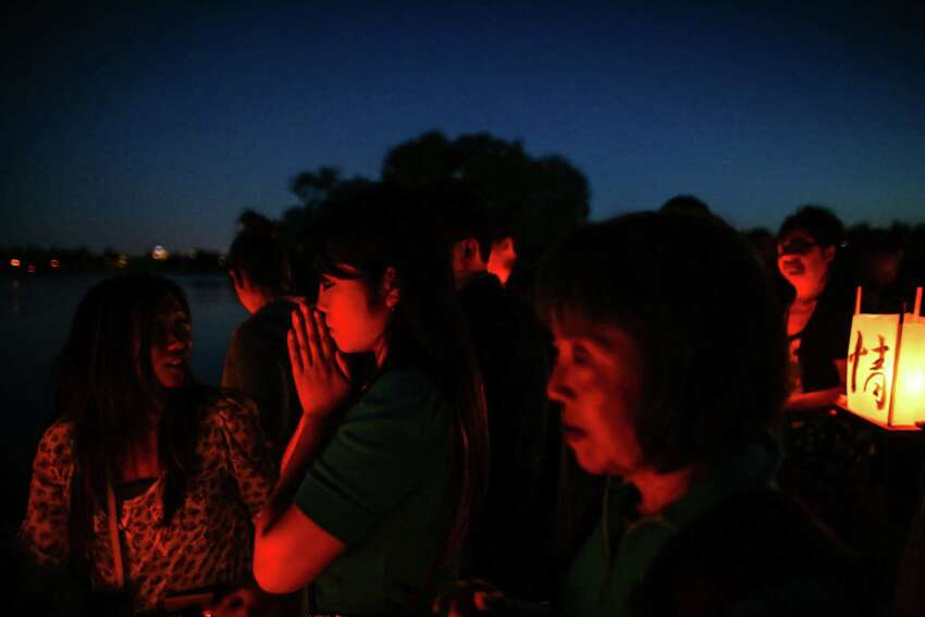 People offer prayers Thursday at Green Lake to honor victims of the atomic bombings of Hiroshima, Nagasaki and other wars. Thousands of people gathered on a dock and the shore of Green Lake on the 70th anniversary of the U.S. use of the atomic bomb to launch floating lanterns. The date has been marked with a ceremony at Green Lake since 1984. Photographed on Thursday, Aug. 6, 2015.