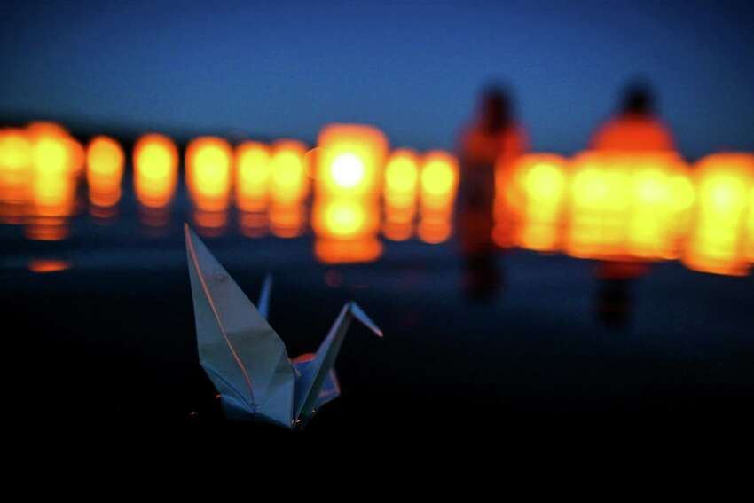 A paper crane floats on the water as people gather at Green Lake on Thursday to honor victims of the atomic bombings of Hiroshima, Nagasaki and other wars. Thousands of people gathered on a dock and the shore of Green Lake on the 70th anniversary of the U.S. use of the atomic bomb to launch floating lanterns. The date has been marked with a ceremony at Green Lake since 1984. Photographed on Thursday, Aug. 6, 2015.