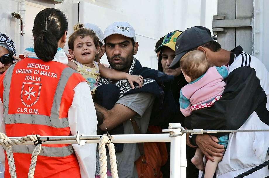 People holding children wait  to disembark the patrol vessel Fiorillo of the Italian Coast Guard as it arrives in the port of Pozzallo on August 7, 2015 after saving some 387 migrants in the Sicilian Channel. AFP PHOTO / GIOVANNI ISOLINOGIOVANNI ISOLINO/AFP/Getty Images Photo: Giovanni Isolino, AFP / Getty Images