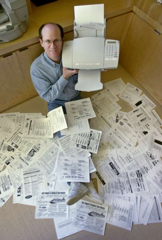 Technology entrepreneur Steve Kirsch holds up his fax machine as he displays junk faxes he received at his home in Los Altos, Calif., in this May 10, 2002, file photo.  Photo: PAUL SAKUMA, File  / AP