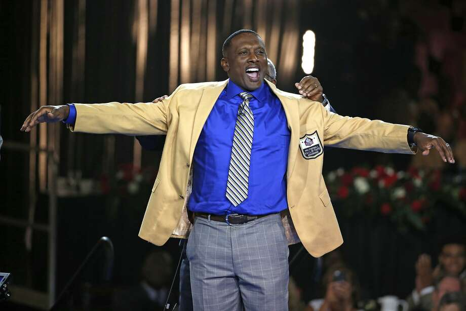 Pro Football Hall of Fame inductee Tim Brown slips on his gold jacket with the help of his presenter, his brother Donald Kelly, rear, during the Gold Jacket Ceremony in Canton, Ohio, Thursday, Aug. 6, 2015. (AP Photo/Gene J. Puskar) Photo: Gene J. Puskar, Associated Press