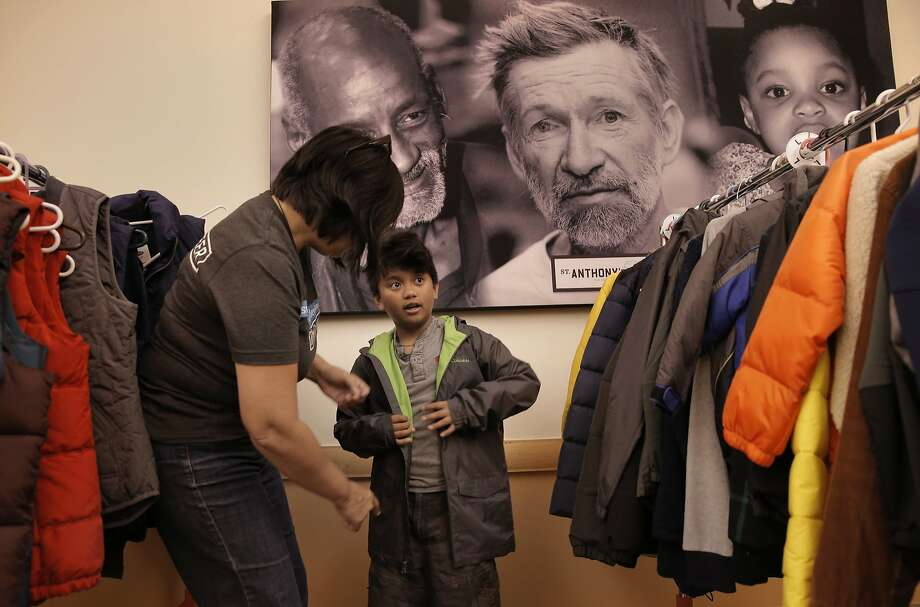 Jethron Revilla Jr., 9 is helped by volunteer Laura Stepping as he tries on a new coat during the St. Anthony's back to school giveaway to get kids ready for the new school year, in San Francisco, Calif., on Fri. August 7, 2015. Photo: Michael Macor, The Chronicle