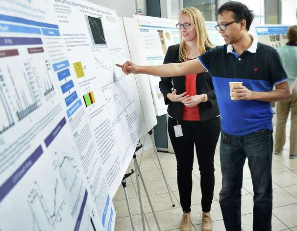 SUNY Poly CNSE Summer Intern Anne Kennedy, left, of Albany, gets some input on her magnetoresistance poster from SUNY Poly PhD student  Zahiruddir Alamgir during their presentations at SUNY Polytechnic Institute Friday Aug. 7, 2015, in Albany, NY.  (John Carl D'Annibale / Times Union) Photo: John Carl D'Annibale / 00032935A