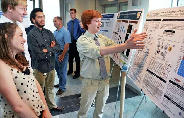 SUNY Poly CNSE Summer Intern Shawn Fidotta, center, explains his poster on CHO cells to fellow students during their final presentations at SUNY Polytechnic Institute Friday Aug. 7, 2015, in Albany, NY.  (John Carl D'Annibale / Times Union) Photo: John Carl D'Annibale / 00032935A