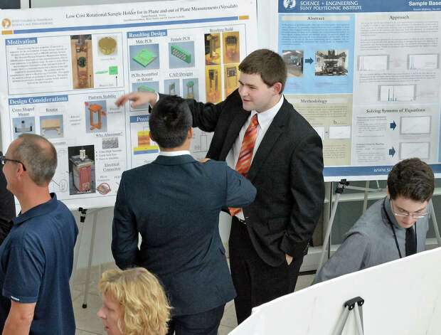 SUNY Poly CNSE Summer Intern Dan Pennock, center, of Ravena shows off his poster on engineering solutions during their final presentations at SUNY Polytechnic Institute Friday Aug. 7, 2015, in Albany, N.Y.  (John Carl D'Annibale / Times Union) Photo: John Carl D'Annibale / 00032935A