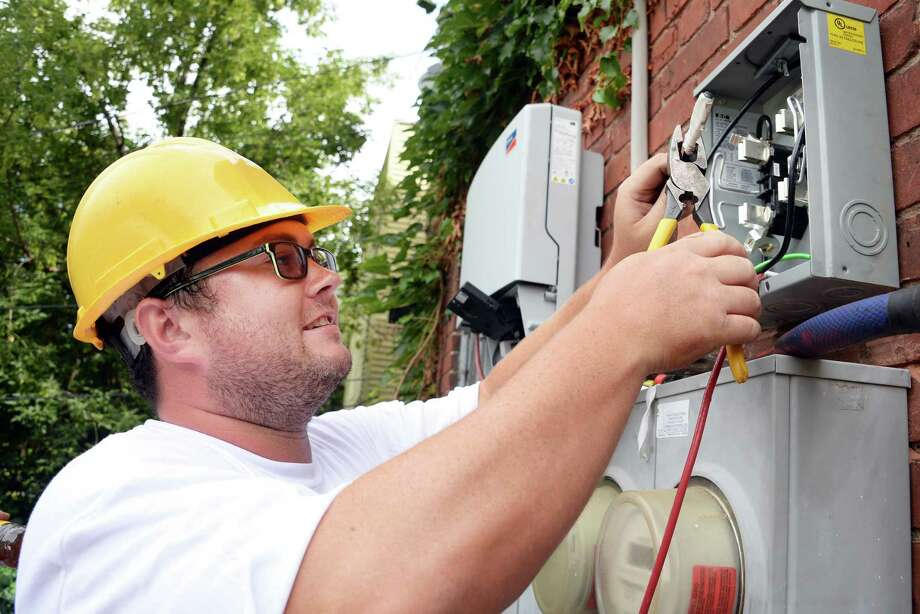 GRID Alternatives volunteer Dean Fagan of Troy wires up a production meter during an the installation of a solar electric system at a 5th Avenue home, the first one to be done by GRID in Upstate New York, Friday August 7, 2015 in Troy, NY. GRID Alternatives is a national non-profit organization that makes renewable energy technology and job training accessible to low-income communities.  (John Carl D'Annibale / Times Union) Photo: John Carl D'Annibale / 10032905A