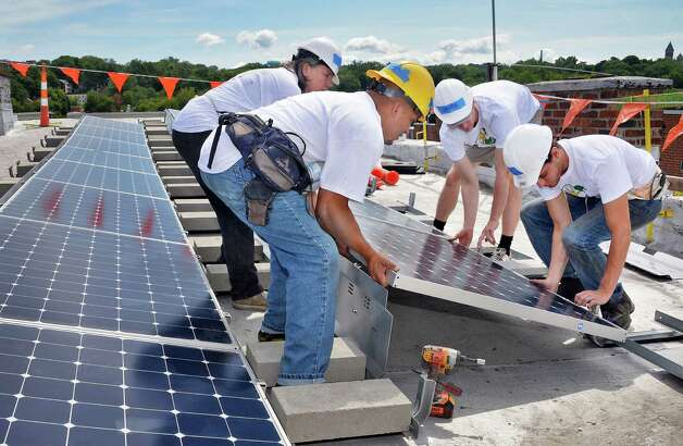 GRID Alternatives volunteers install a solar electric system panel at a 5th Avenue home, the first one to be done by GRID in Upstate New York, Friday August 7, 2015 in Troy, NY. GRID Alternatives is a national non-profit organization that makes renewable energy technology and job training accessible to low-income communities.  (John Carl D'Annibale / Times Union) Photo: John Carl D'Annibale / 10032905A
