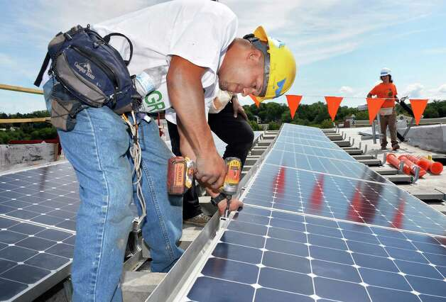GRID Alternatives volunteer Shane Velez of the Bronx installs a solar electric system panel at a 5th Avenue home, the first one to be done by GRID in Upstate New York, Friday August 7, 2015 in Troy, NY. GRID Alternatives is a national non-profit organization that makes renewable energy technology and job training accessible to low-income communities.  (John Carl D'Annibale / Times Union) Photo: John Carl D'Annibale / 10032905A
