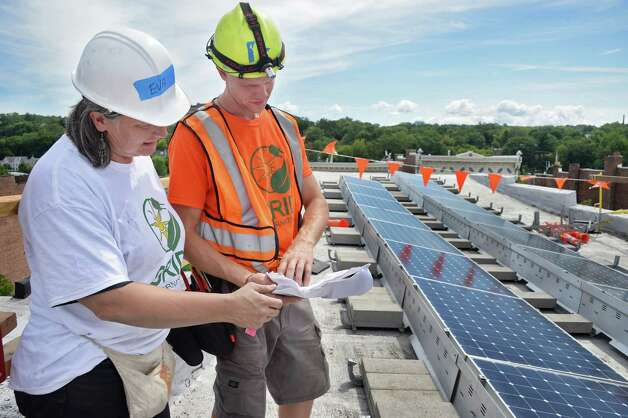 GRID Alternatives volunteer Eva Lewandowski, left, and solar installation supervisor Orrie Bossin review plans for a solar electric system panel atop the roof a 5th Avenue home, the first one to be done by GRID in Upstate New York, Friday August 7, 2015 in Troy, NY. GRID Alternatives is a national non-profit organization that makes renewable energy technology and job training accessible to low-income communities.  (John Carl D'Annibale / Times Union) Photo: John Carl D'Annibale / 10032905A