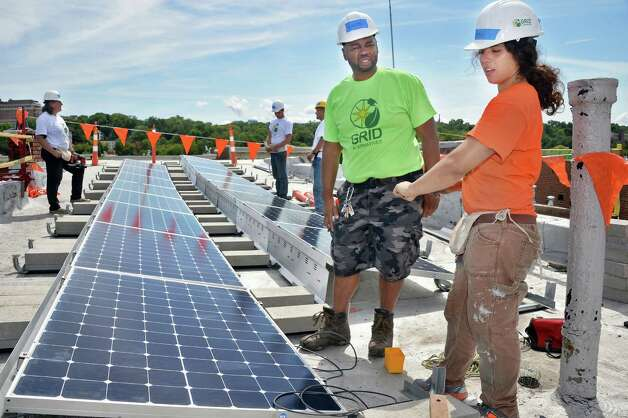 GRID Alternatives construction assistant Kyrstal Ruiz, right, speaks with home owner David Anderson on the roof of his 5th Avenue home as a group of volunteers install a solar electric system, the first one to be done by GRID in Upstate New York. Friday August 7, 2015 in Troy, NY. GRID Alternatives is a national non-profit organization that makes renewable energy technology and job training accessible to low-income communities.  (John Carl D'Annibale / Times Union) Photo: John Carl D'Annibale / 10032905A
