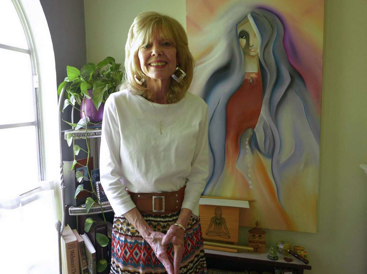"""Tranette Ledford deals with pelvic radiation disease every day. She is a journalist who worked for CNN and covered the Geraldine Ferraro campaign during the 1984 presidential race. She is also an accomplished artist. She calls the painting behind her """"Feminine Divine Presence,"""" which she patterned after a statue that she saw in New Mexico."""