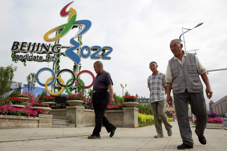Chinese men walk past the Beijing 2022 Olympic bid logo in the mountain town of Chongli which will host the 2022 Nordic skiing, ski jumping, and other outdoor Winter Olympic events in northern China's Hebei province. Photo: Ng Han Guan /Associated Press / AP