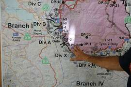 Public Information Officer Ron Oatman discusses a map that shows the updated fire situation at the briefing area in the incident base camp August 6, 2015 in Lakeport, Calif. The camp is set up in the fairgrounds of Lakeport and it provides food, water, bathrooms, sleeping areas, vehicle and tool maintenance, medical care along with an entire planning division used for strategizing the fire fighting. The camp has been supporting over 3,000 firefighters and emergency personnel since the beginning of the fire.