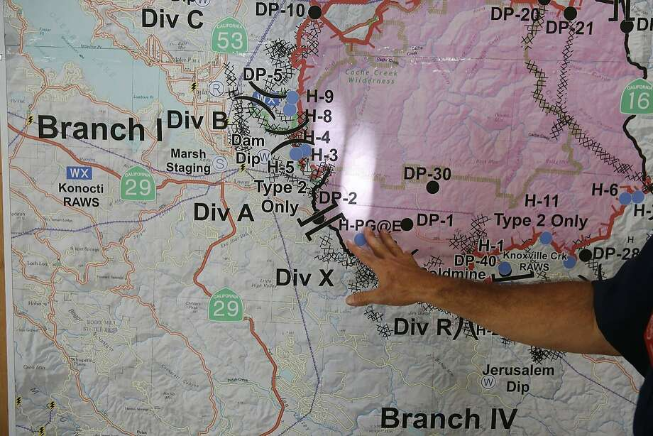 Public Information Officer Ron Oatman discusses a map that shows the updated fire situation at the briefing area in the incident base camp August 6, 2015 in Lakeport, Calif. The camp is set up in the fairgrounds of Lakeport and it provides food, water, bathrooms, sleeping areas, vehicle and tool maintenance, medical care along with an entire planning division used for strategizing the fire fighting. The camp has been supporting over 3,000 firefighters and emergency personnel since the beginning of the fire. Photo: Leah Millis, The Chronicle