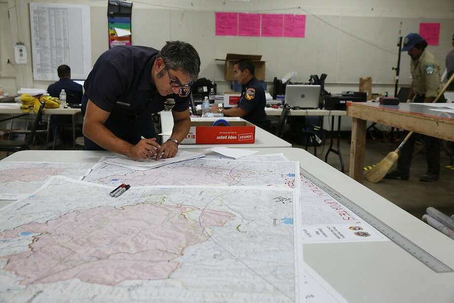 Jay Sartoris works on updating maps from the verified information he has received from the field in the Rocky Fire at the incident base camp August 6, 2015 in Lakeport, Calif. The camp is set up in the fairgrounds of Lakeport and it provides food, water, bathrooms, sleeping areas, vehicle and tool maintenance, medical care along with an entire planning division used for strategizing the fire fighting. The camp has been supporting over 3,000 firefighters and emergency personnel since the beginning of the fire. Photo: Leah Millis, The Chronicle