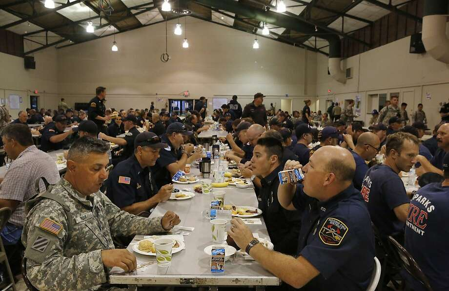From left, Staff Sg't Anthony Trout, Nevada County's Lance McKinley, Aaron Maddox and Derek Sweet chat as they eat breakfast at the incident base camp August 7, 2015 in Lakeport, Calif. The camp is set up in the fairgrounds of Lakeport and it provides food, water, bathrooms, sleeping areas, vehicle and tool maintenance, medical care along with an entire planning division used for strategizing the fire fighting. The camp has been supporting over 3,000 firefighters and emergency personnel since the beginning of the fire. Photo: Leah Millis, The Chronicle