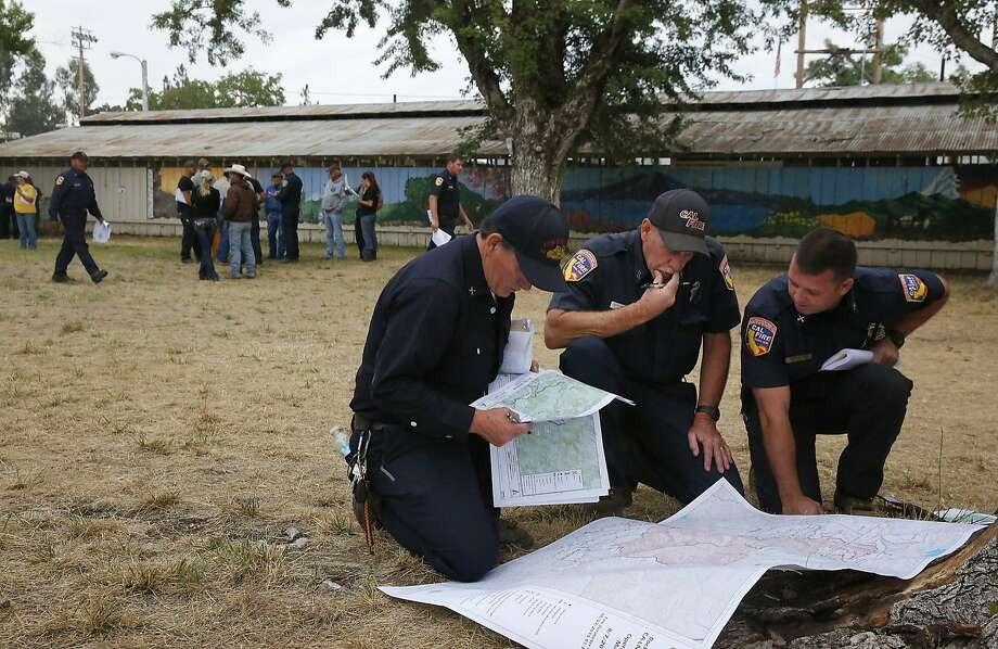 From left, Tom Oakley from Contra Costa County, Division Officer Ken Pridmore of Sonoma Lake Napa and Sean Norman from Butte formulate their strategy for the day at the incident base camp August 7, 2015 in Lakeport, Calif. The camp is set up in the fairgrounds of Lakeport and it provides food, water, bathrooms, sleeping areas, vehicle and tool maintenance, medical care along with an entire planning division used for strategizing the fire fighting. The camp has been supporting over 3,000 firefighters and emergency personnel since the beginning of the fire. Photo: Leah Millis, The Chronicle