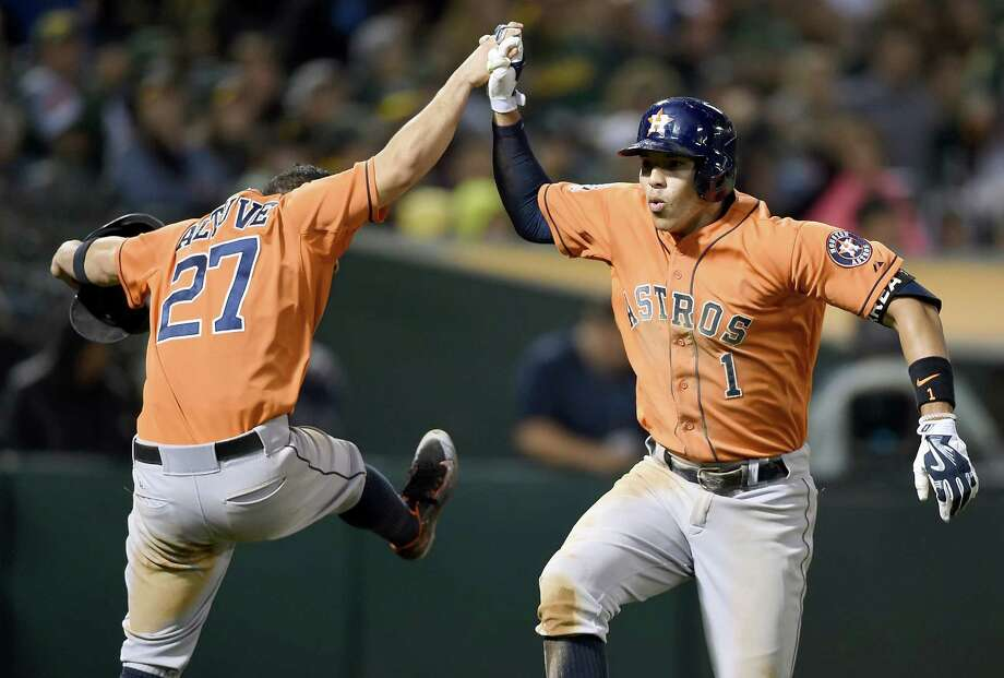 OAKLAND, CA - AUGUST 06:  Carlos Correa #1 and Jose Altuve #27 of the Houston Astros celebrates after Correa hit a two-run homer against the Oakland Athletics in the top of the eighth inning at O.co Coliseum on August 6, 2015 in Oakland, California.  (Photo by Thearon W. Henderson/Getty Images) Photo: Thearon W. Henderson, Stringer / 2015 Getty Images