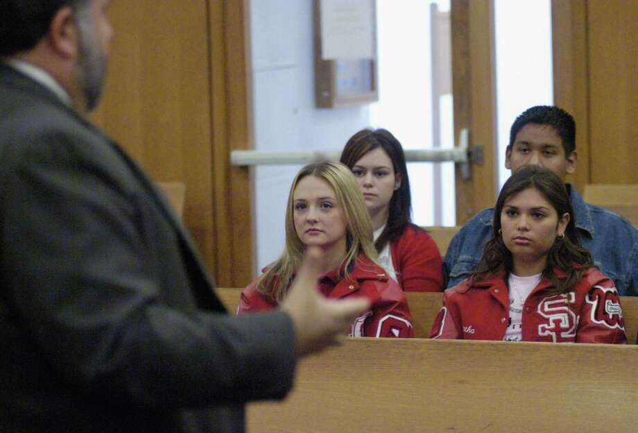 Samantha Jordan and Denes Larivea from South Houston High School listen to attorney Joe Indelicato  in Judge Lemkuil's court Friday Nov.5, 2004.(Dave Rossman/For the Chronicle)    HOUCHRON CAPTION (11/18/2004) THIS WEEK Z3:  SOUTH Houston High School students Samantha Jordan and Denes Larivea listen as attorney Joe Indelicato explains the jury selection process in District Judge Daniel Lemkuil's court. The students recently participated in a Houston Bar Association-sponsored program that seeks to educate high school students, who will soon be eligible for jury service, about the voir dire process and how juries are selected. Photo: Dave Rossman, Freelance / freelance