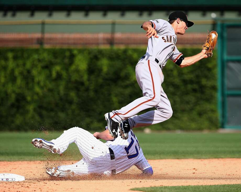 Kris Bryant #17 of the Chicago Cubs steals second base under Kelby Tomlinson #37 of the San Francisco Giants who leaps to make the catch at Wrigley Field on August 7, 2015 in Chicago, Illinois.  Photo: Jonathan Daniel, Getty Images