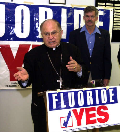 Archbishop Patrick Flores speaks about fluoride with Mayor Howard Peak at the Barrio Comprehensive Family Health Care Center. The bishop urged people to get out and vote. Photo: Express-News File Photo / SAN ANTONIO EXPRESS-NEWS