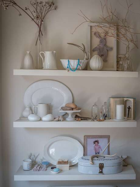Leigh Noë's S.F. home mixes high and low, vintage and new. Here, white ceramic dishes and plates share shelving with a child's well-worn bunny (top left) that she found and framed. Photo: John Storey, Special To The Chronicle